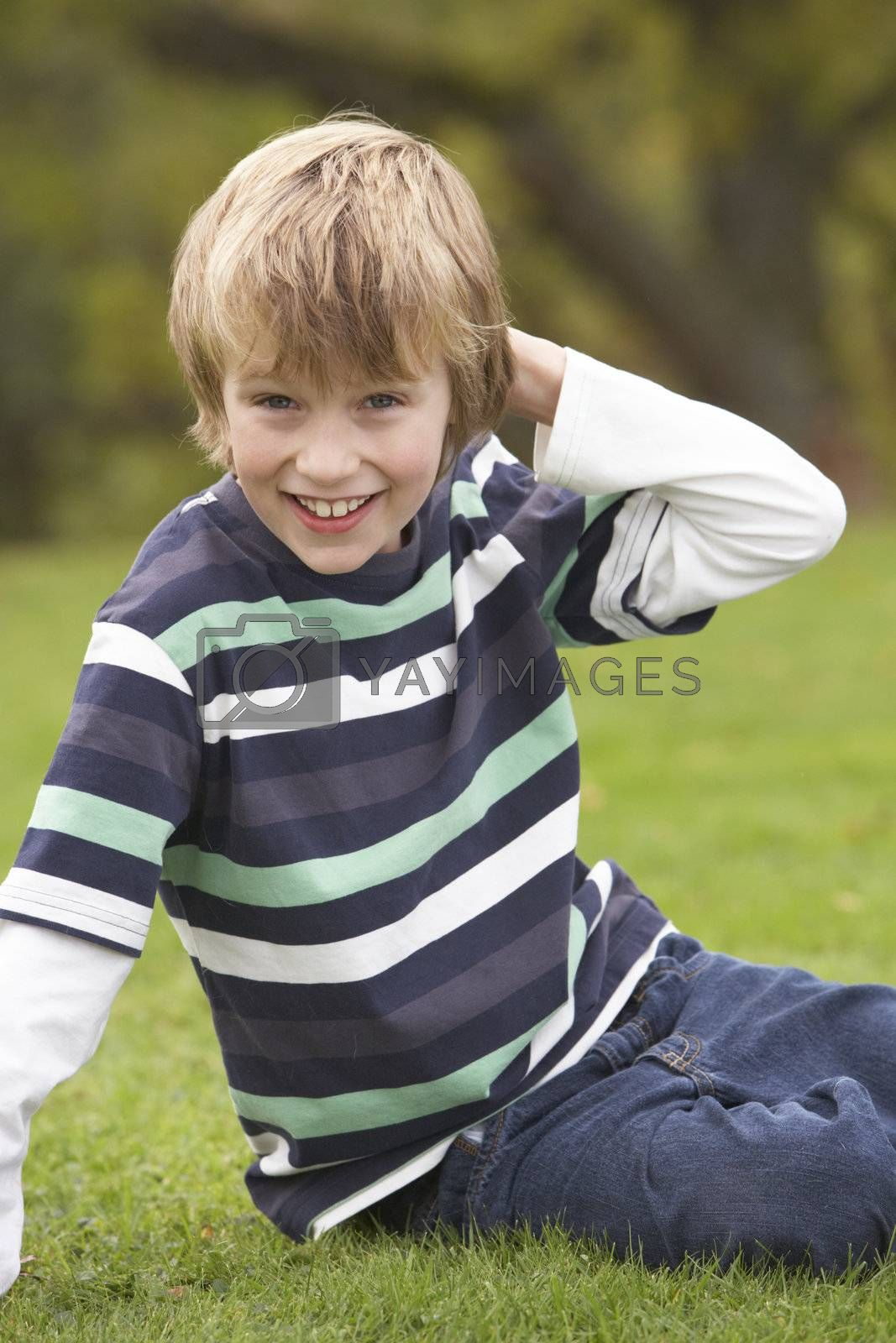 Young Boy Relaxing Outdoors Sitting On Grass