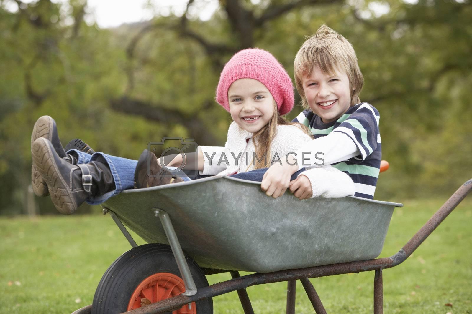 Boy And Girl Sitting In Wheelbarrow