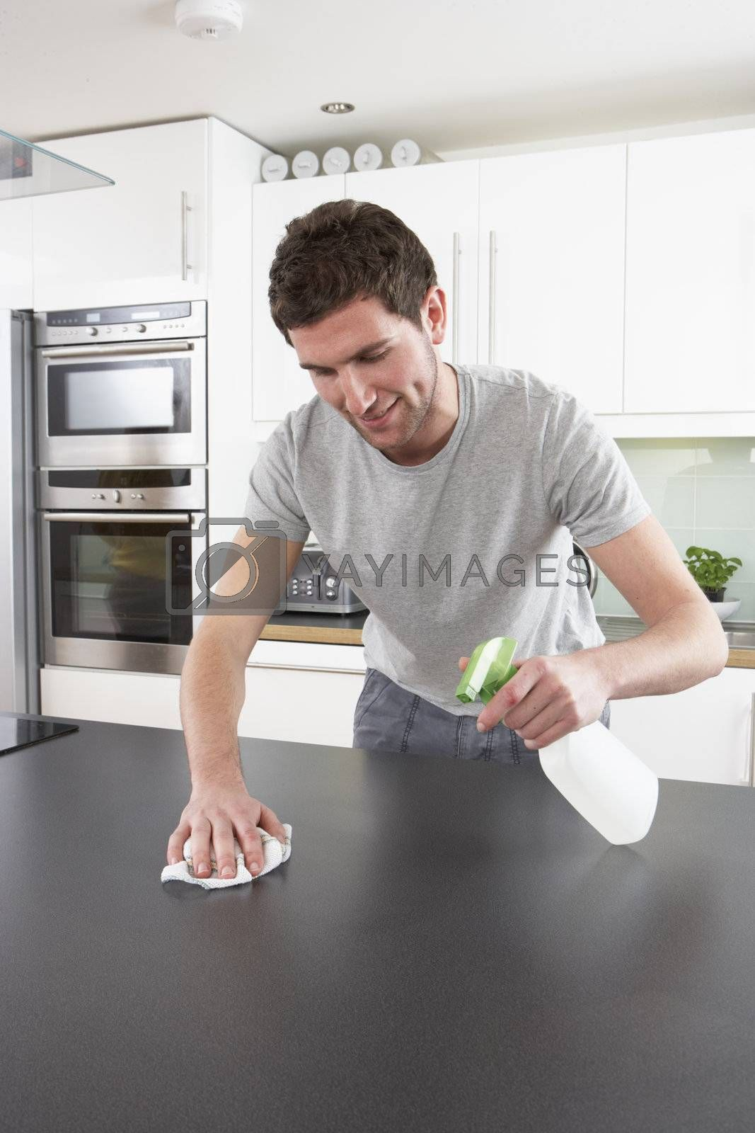 Young Man Cleaning Modern Kitchen