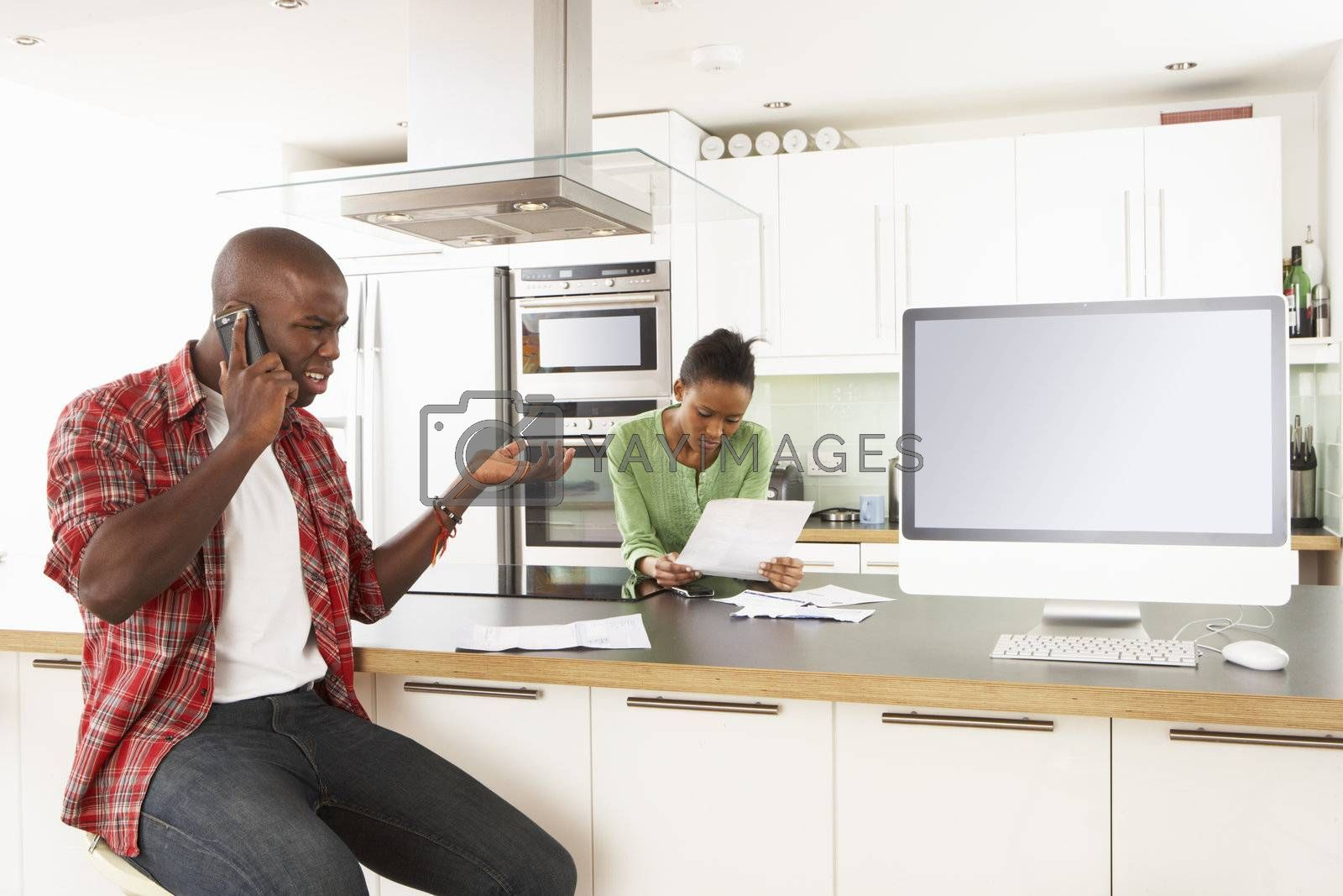 Young Couple Discussing Personal Finances In Modern Kitchen