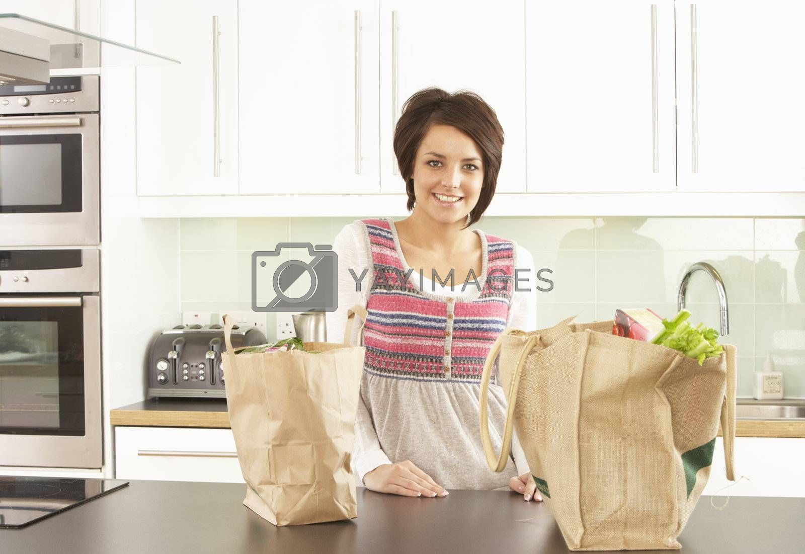 Young Woman Unpacking Shopping In Modern Kitchen