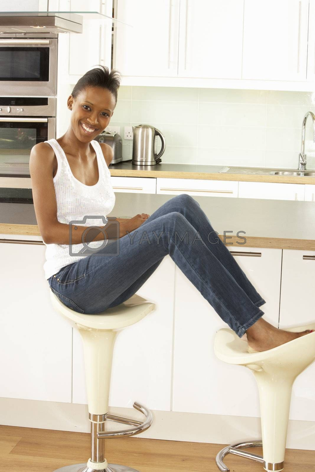 Young Woman Relaxing Sitting In Modern Kitchen