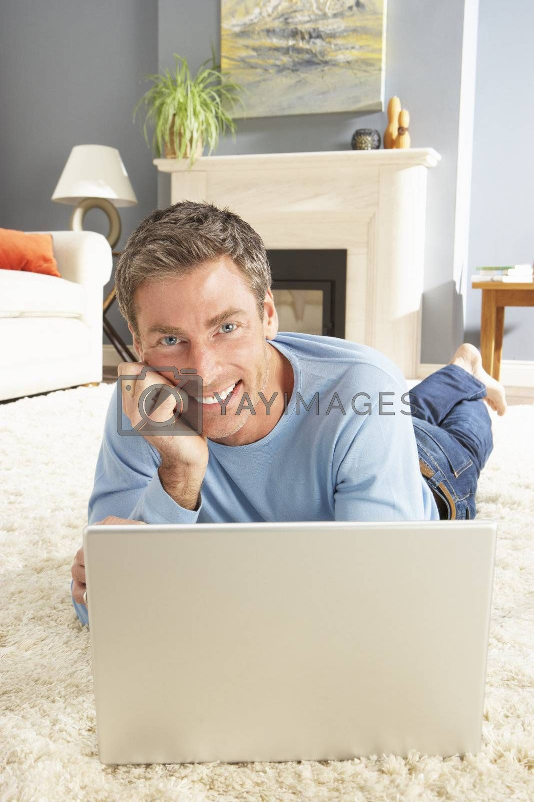 Man Using Laptop Relaxing Laying On Rug At Home