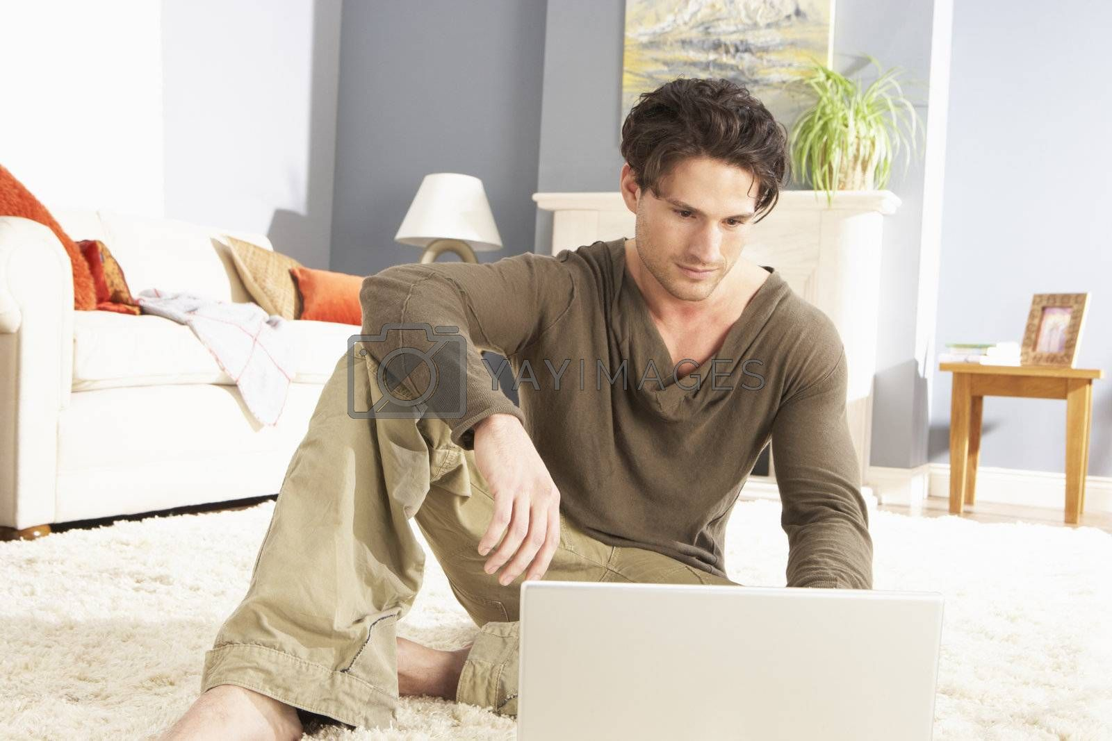 Man Using Laptop Relaxing Sitting On Rug At Home