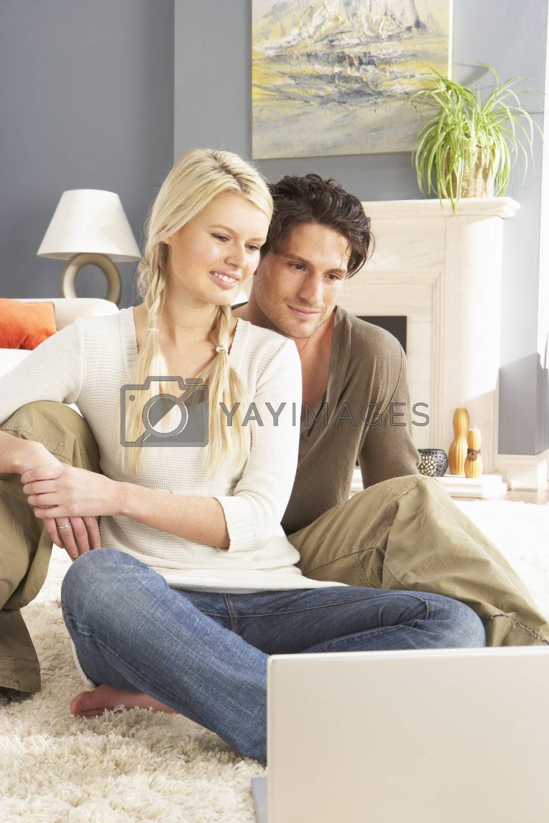 Couple Using Laptop Relaxing Sitting On Rug At Home