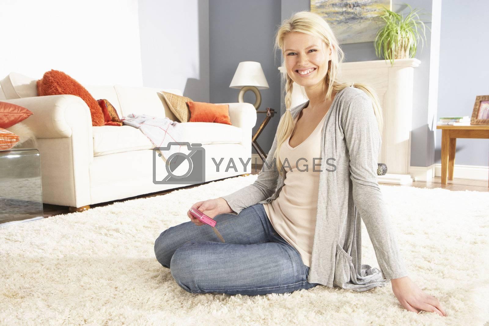 Young Woman Looking At Photograph On Digital Camera At Home