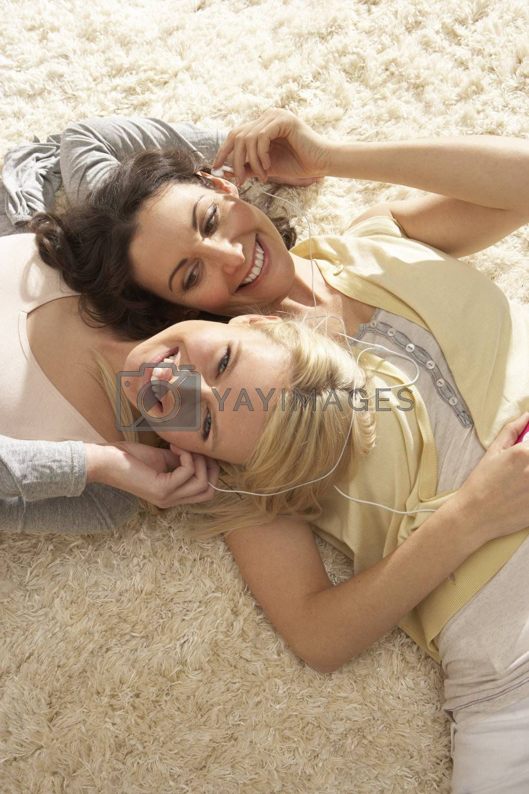 Two Women Listening To MP3 Player On Headphones Together Relaxing Laying On Rug At Home
