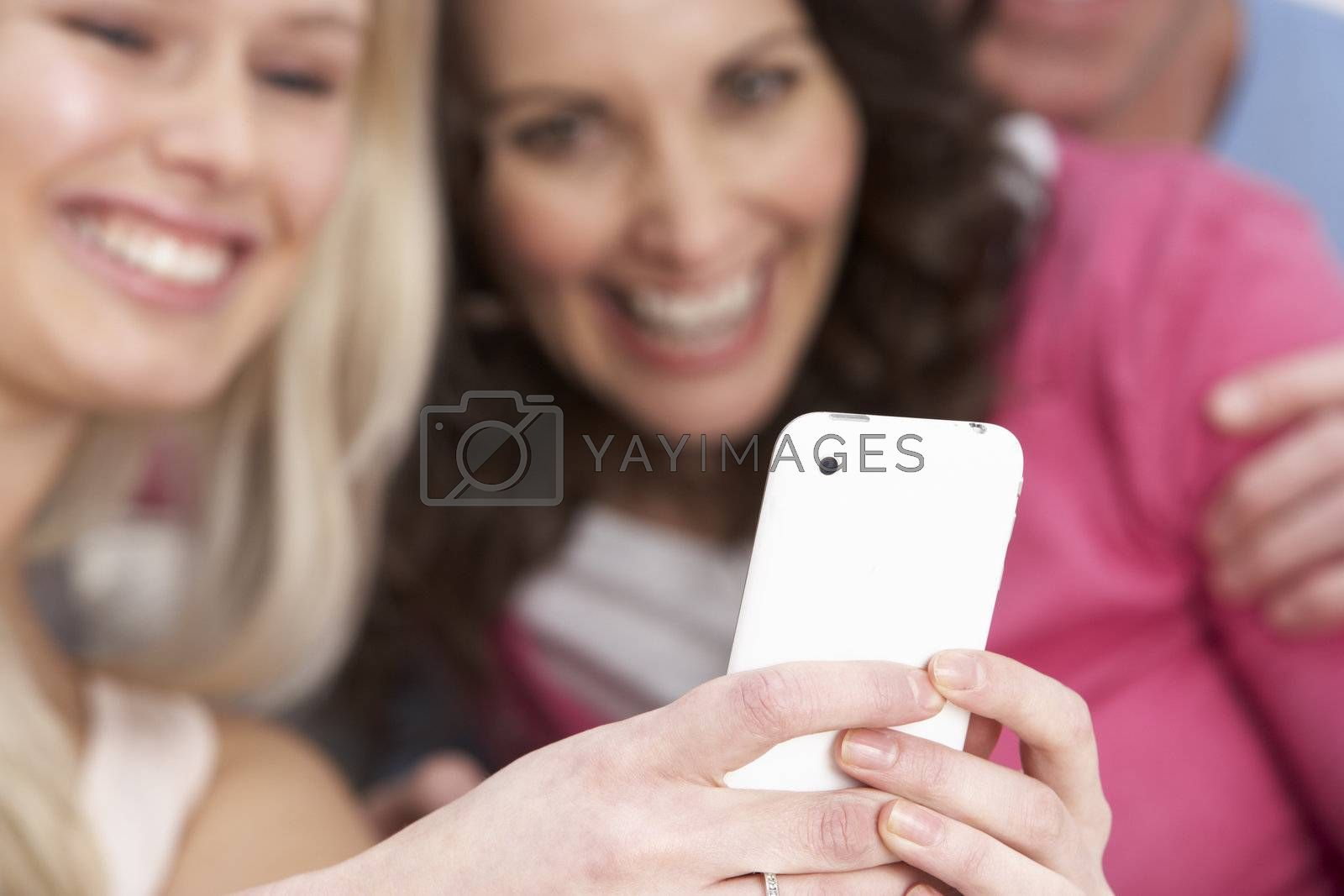 Two Girlfriends Looking At Pictures On Smartphone At Home