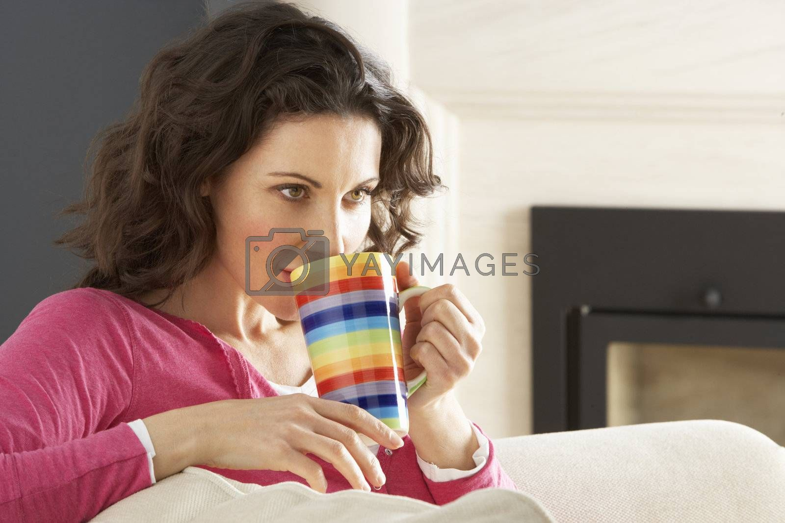 Woman Relaxing On Sofa At Home Drinking Cup Of Coffee
