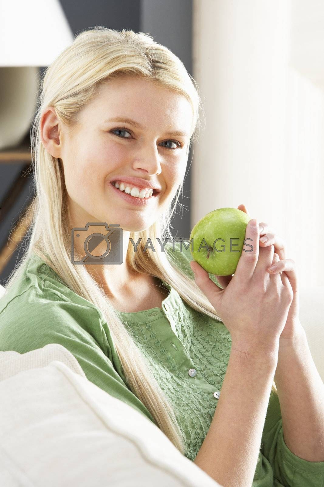 Woman Relaxing On Sofa Eating Apple At Home