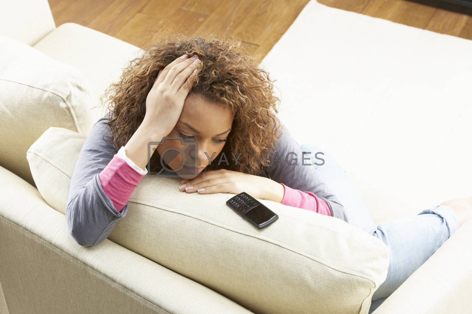 Woman Sitting On Sofa Wating For Mobile Phone At Home