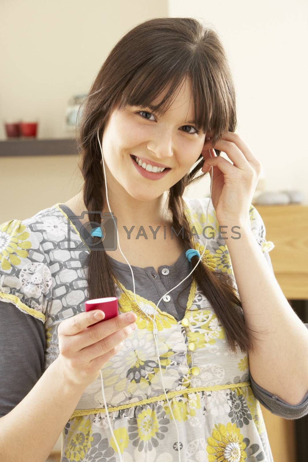 Woman Listening To MP3 Player On Headphones Relaxing Sitting On Rug At Home
