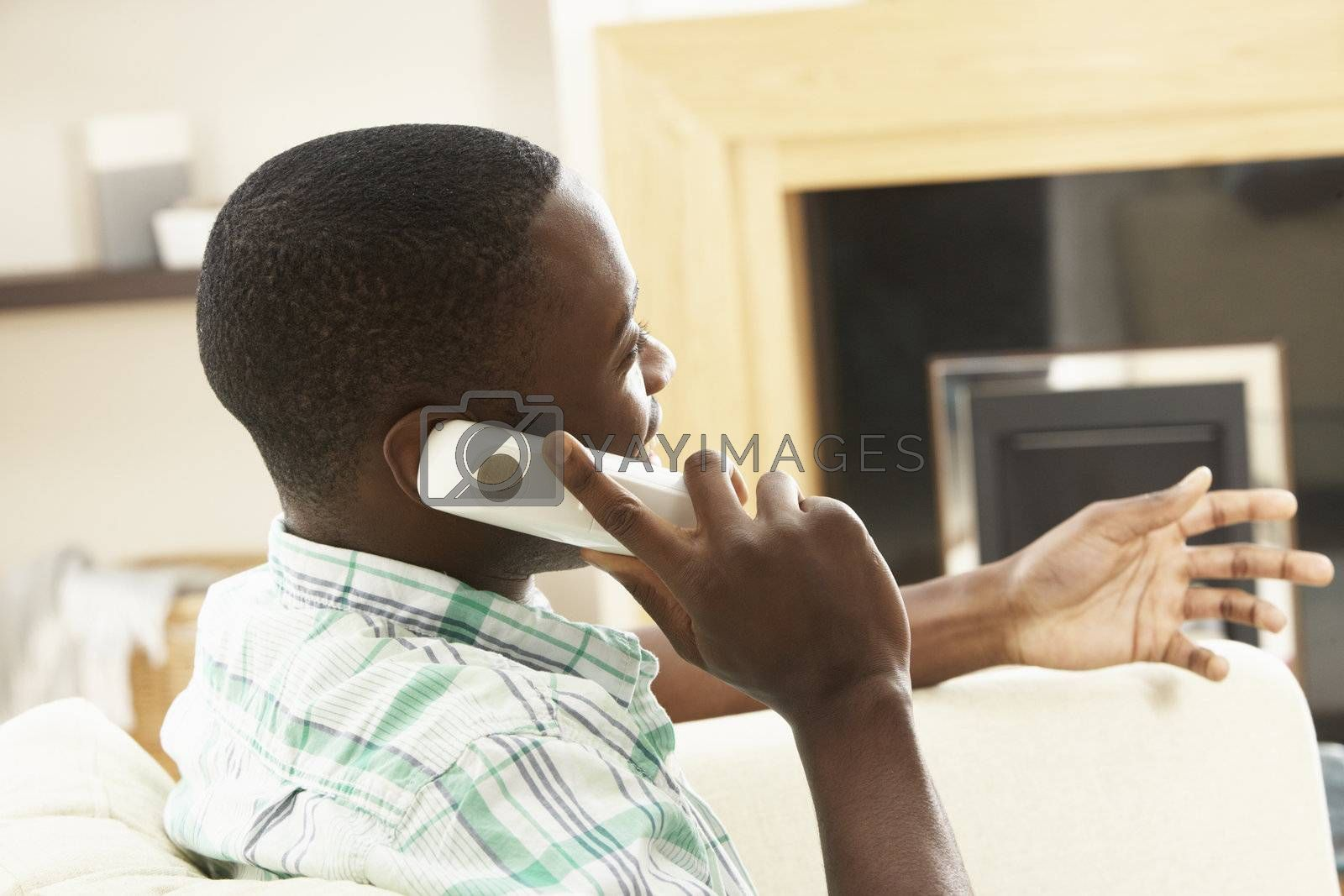 Young Man Relaxing Sitting On Sofa At Home Talking On Phone