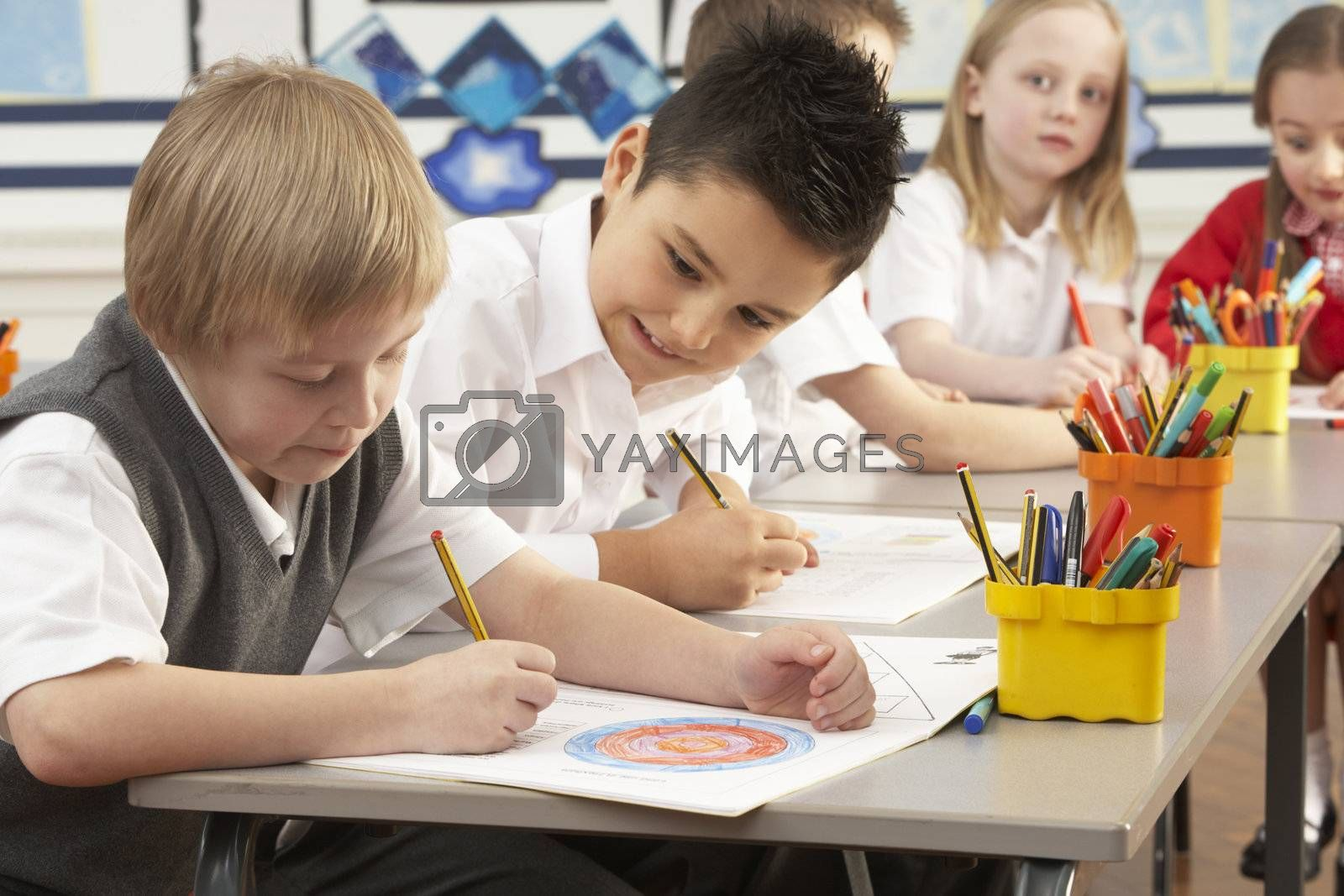 Group Of Primary Schoolchildren In Classroom Working At Desks