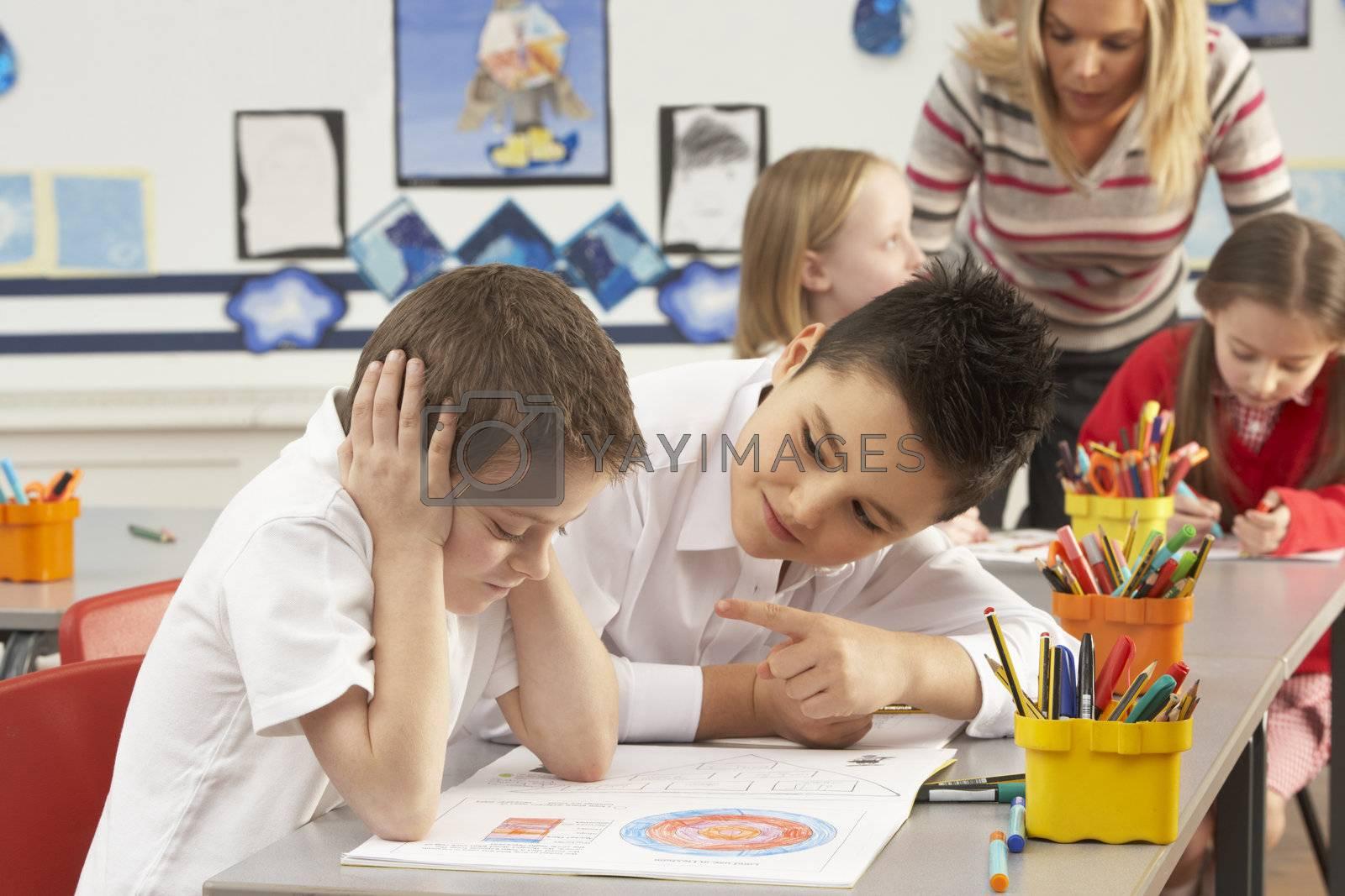 Group Of Primary Schoolchildren And Teacher Working At Desks In Classroom