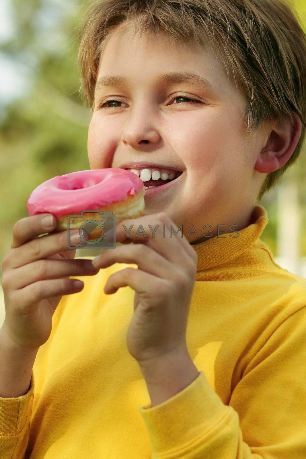 Child eating a pink doughnut by lovleah