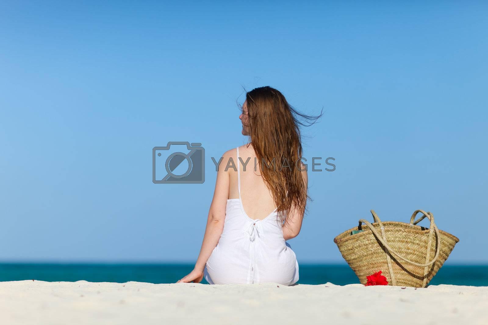 Beautiful girl with beach bag sitting on tropical beach of Zanzibar island