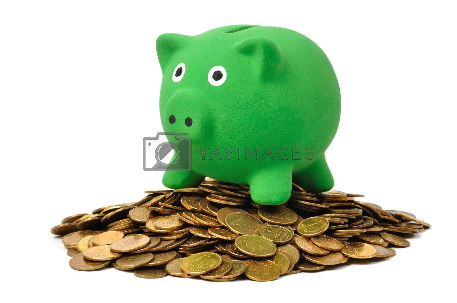 Green piggy bank on coins stack isolated on white