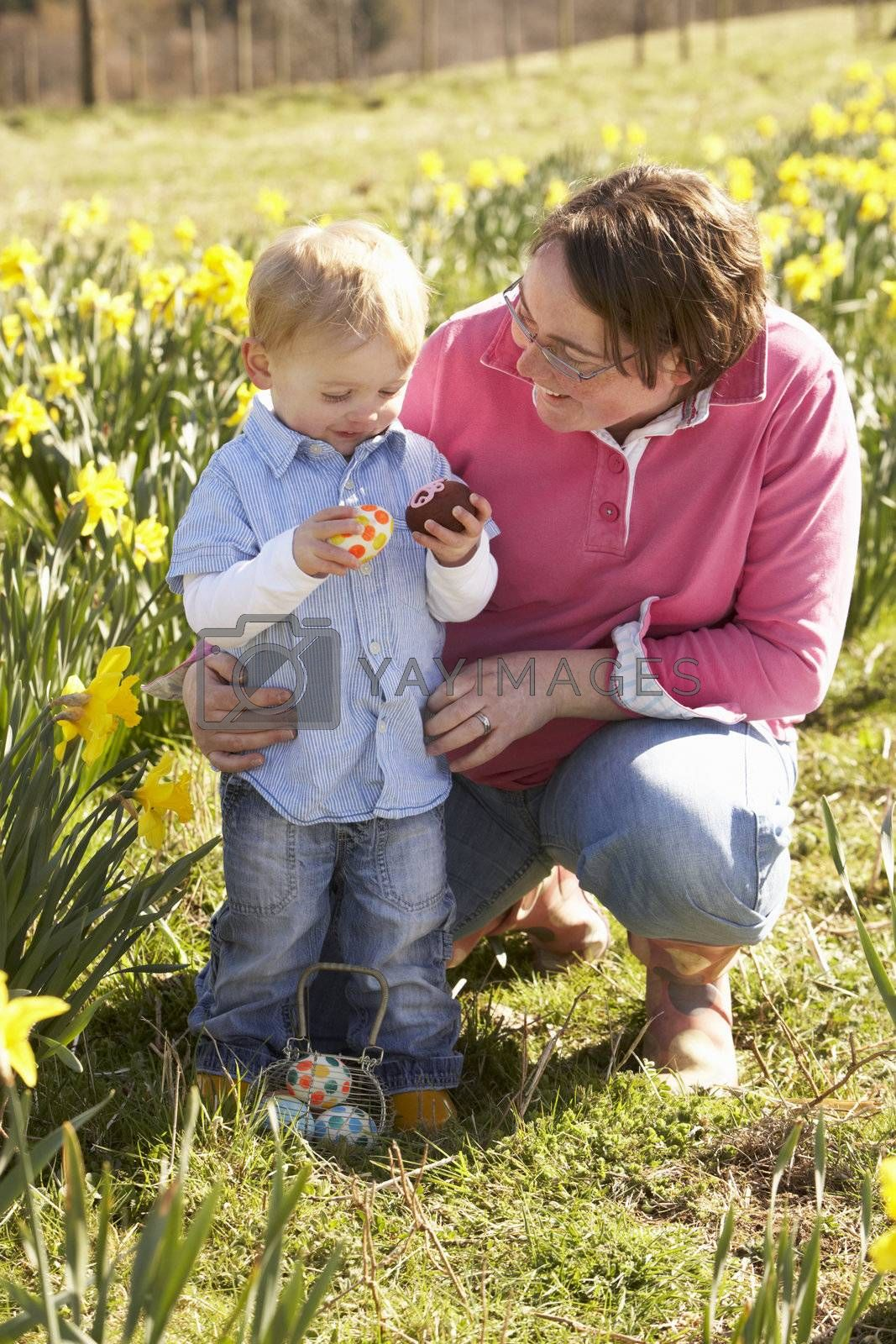 Mother And Son On Easter Egg Hunt In Daffodil Field by OMG Images