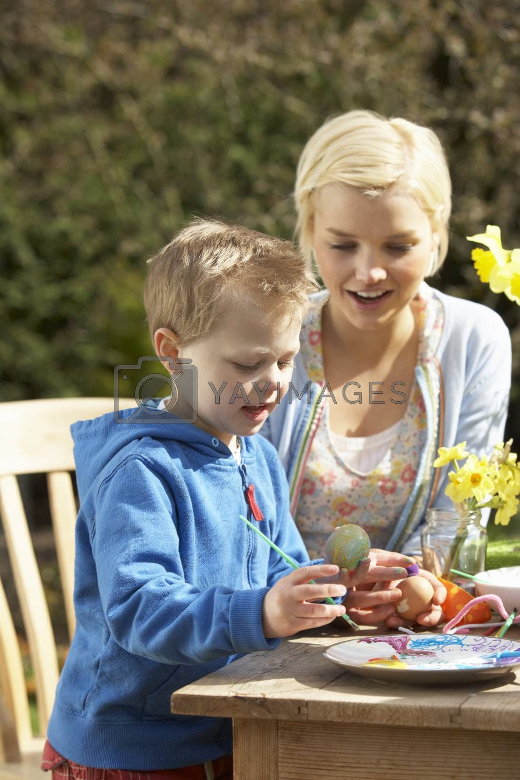 Mother And Son Decorating Easter Eggs On Table Outdoors by OMG Images