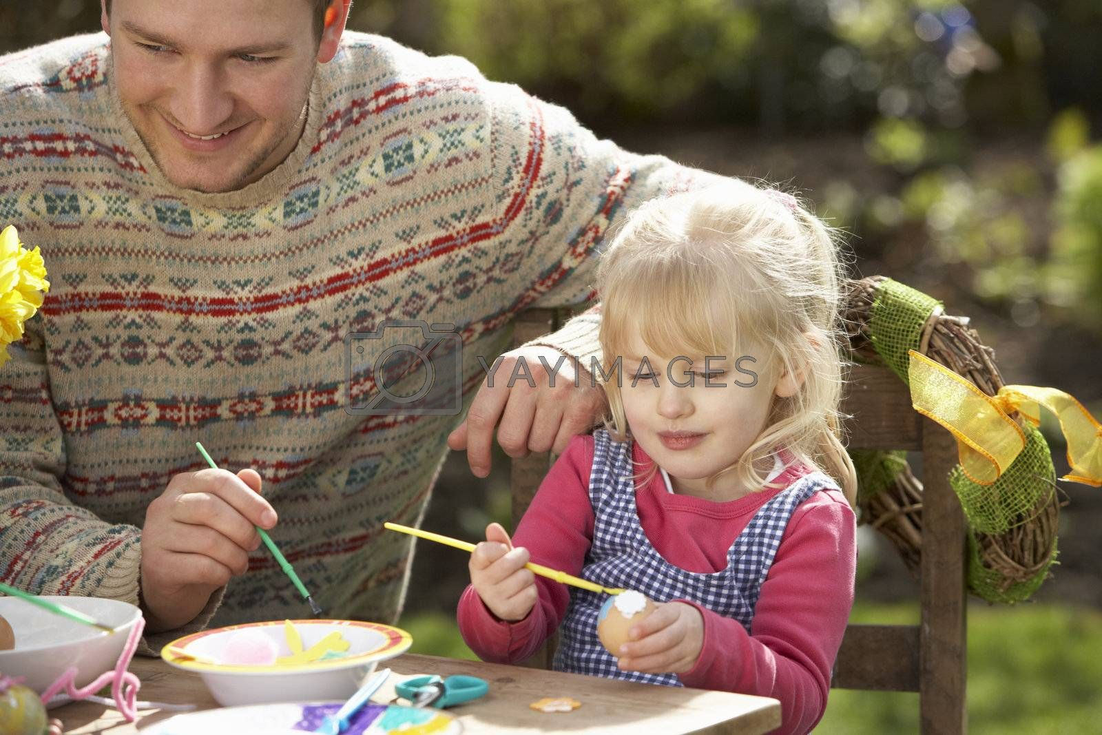 Father And Daughter Decorating Easter Eggs On Table Outdoors by OMG Images