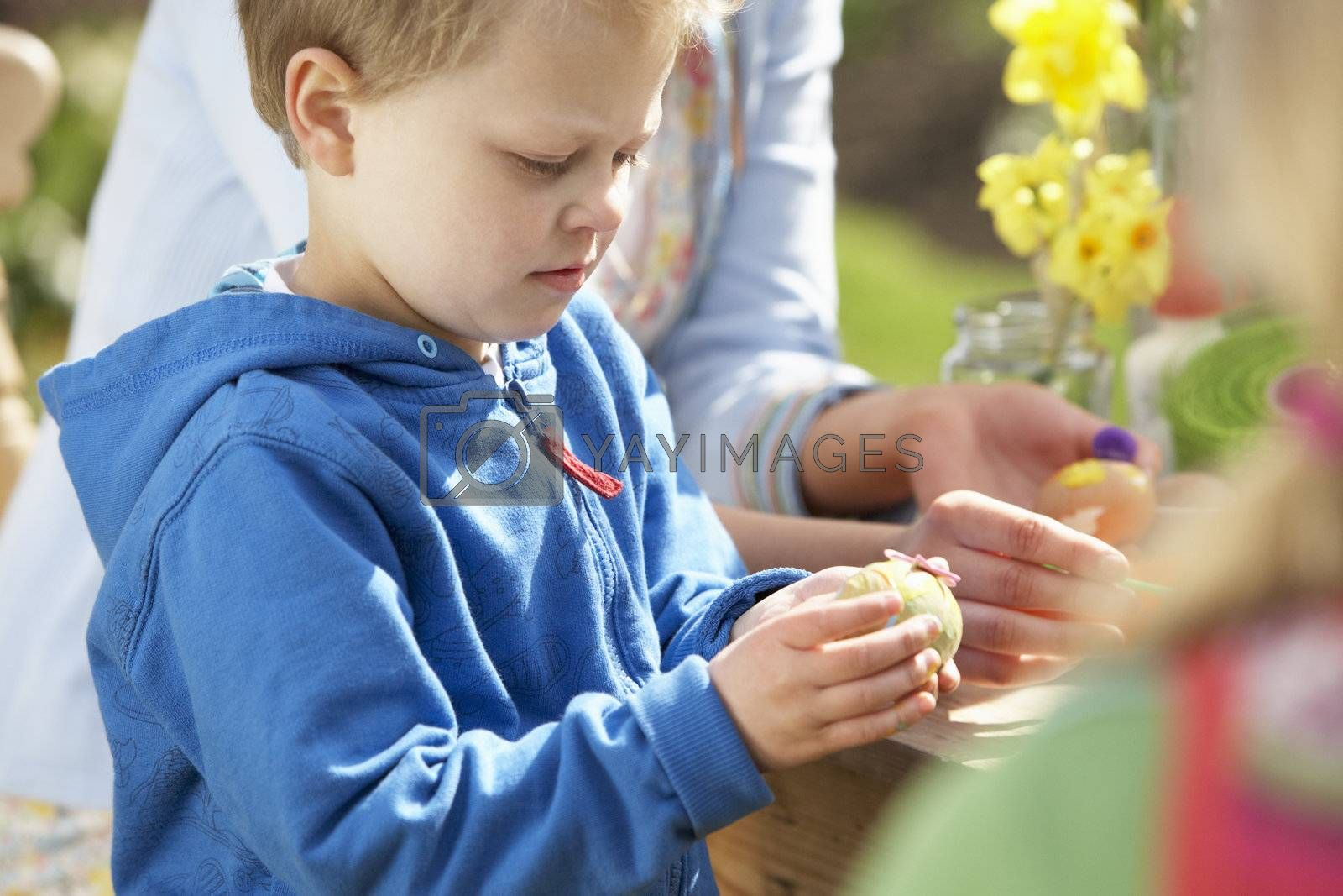 Mother And Children Decorating Easter Eggs On Table Outdoors by OMG Images