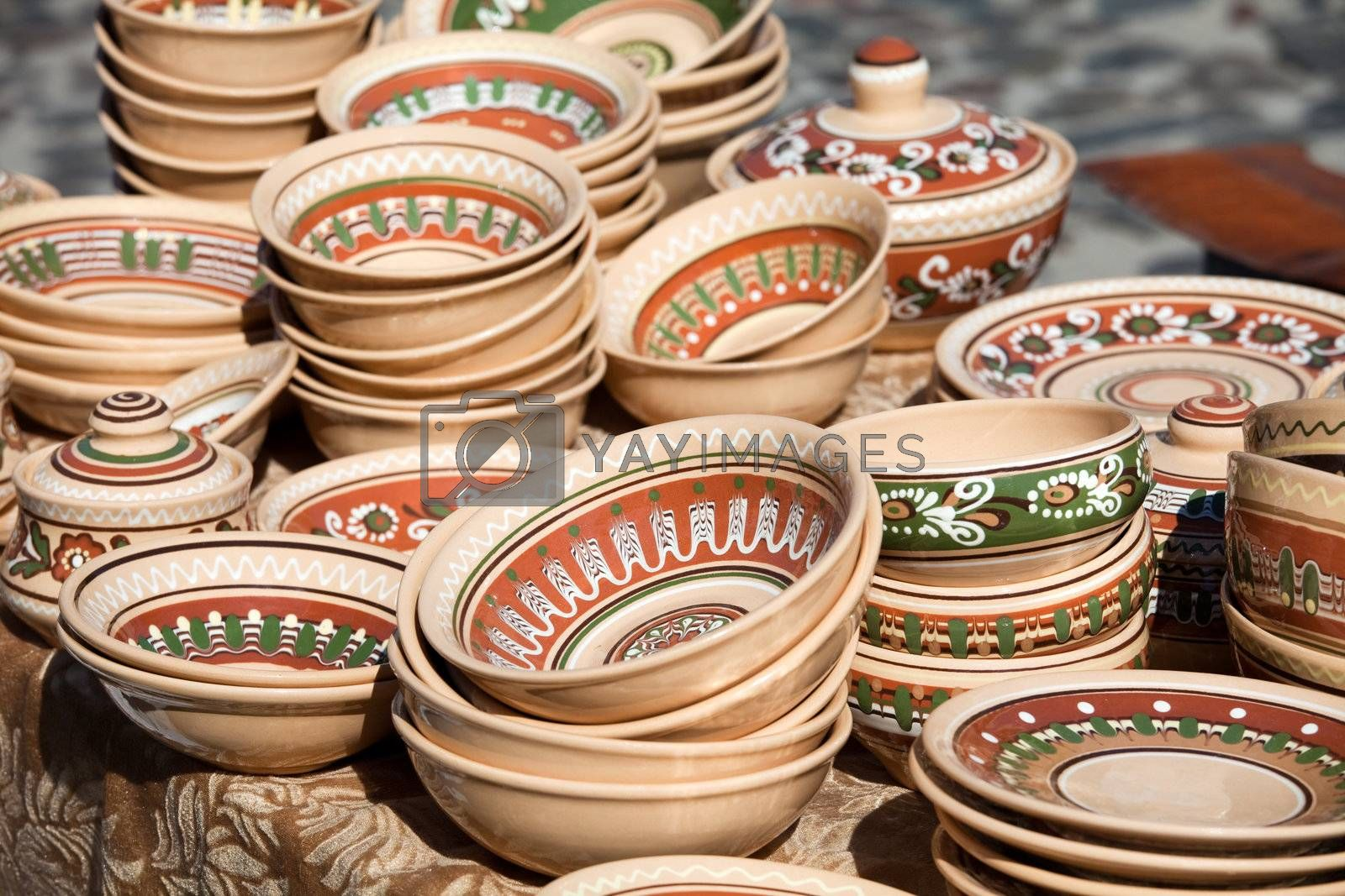 Rustic handmade ceramic and clay brown pots decorated by traditional ornament and pattern at the handicraft market