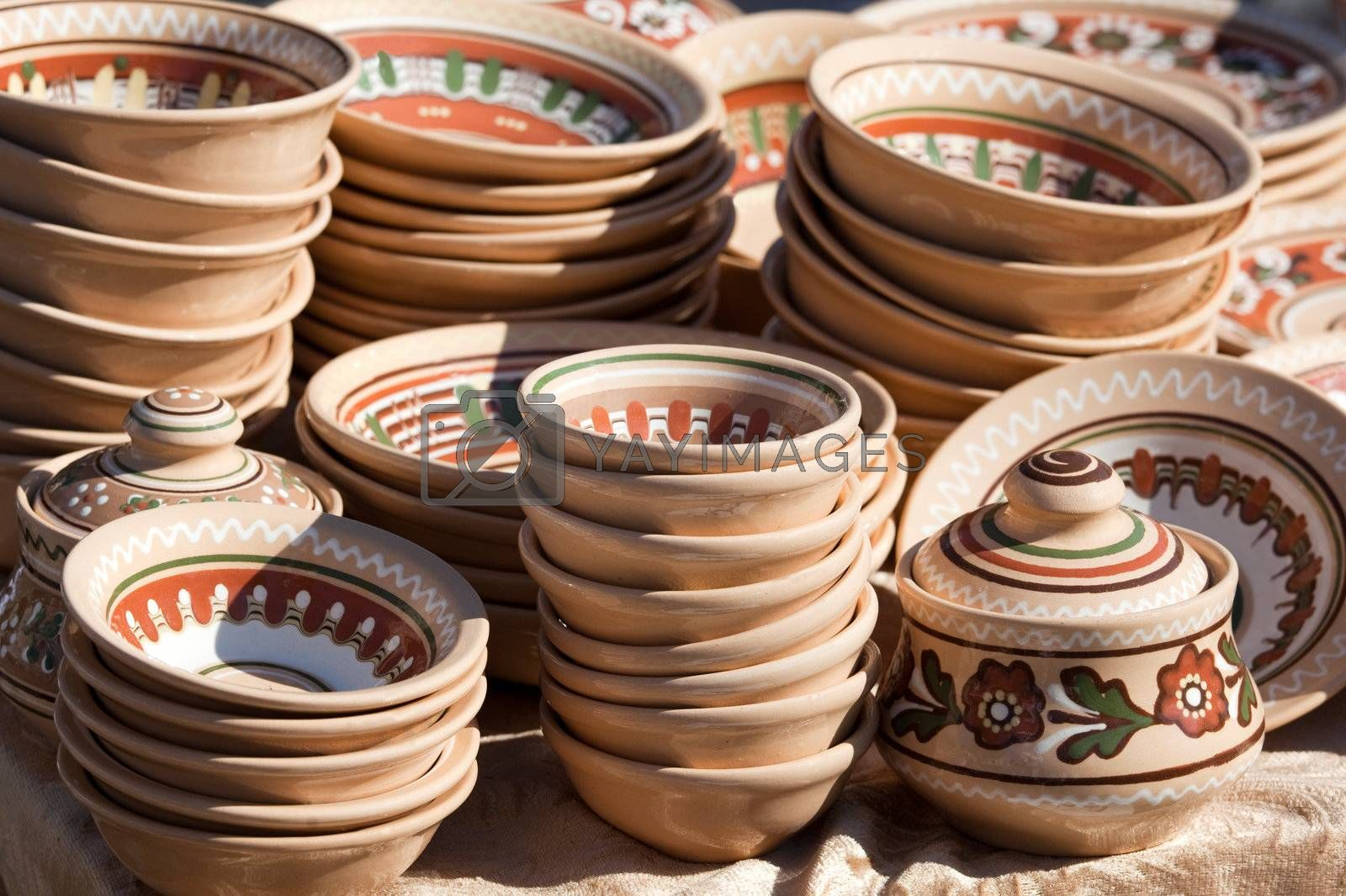 Stack of rustic handmade ceramic brown plates and pots decorated by traditional ornament and pattern at the handicraft market