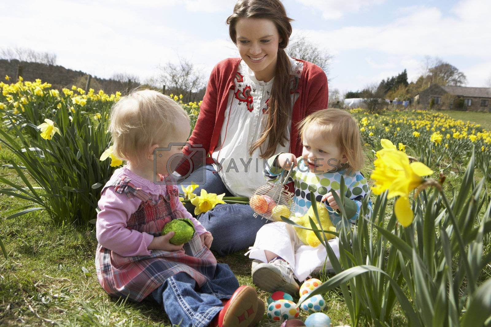 Mother And Daughter In Daffodil Field With Decorated Easter Eggs by OMG Images