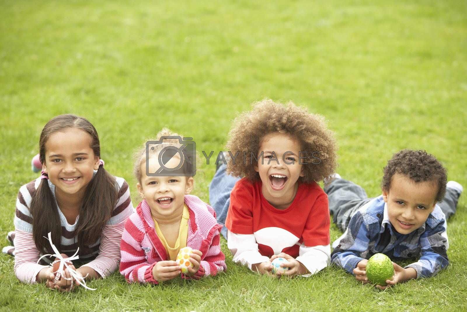 Royalty free image of Group Of Children Laying On Grass With Easter Eggs by omg_images