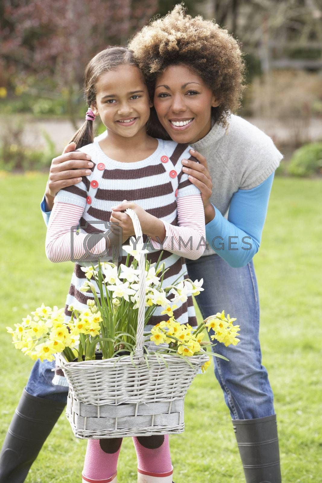 Mother And Daughter Holding Basket Of Daffodils In Garden by OMG Images