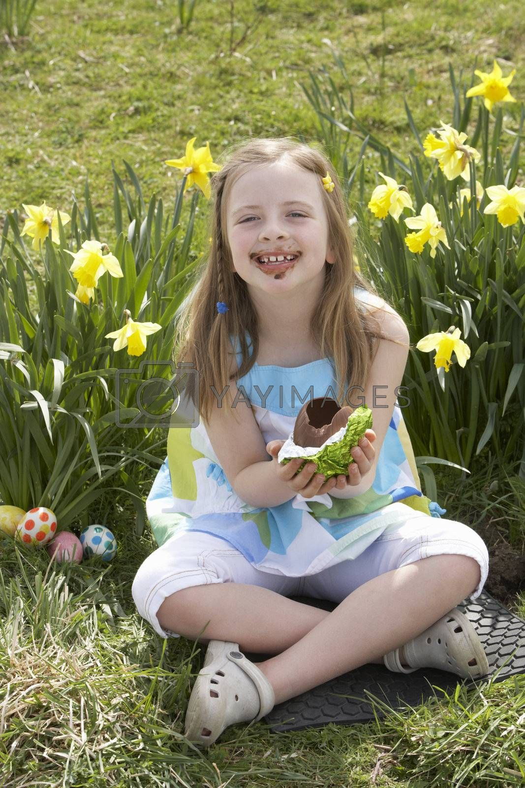 Royalty free image of Girl Eating Chocolate Egg On Easter Egg Hunt In Daffodil Field by omg_images