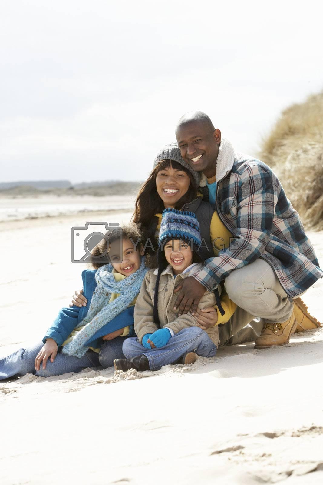 Family Sitting On Winter Beach