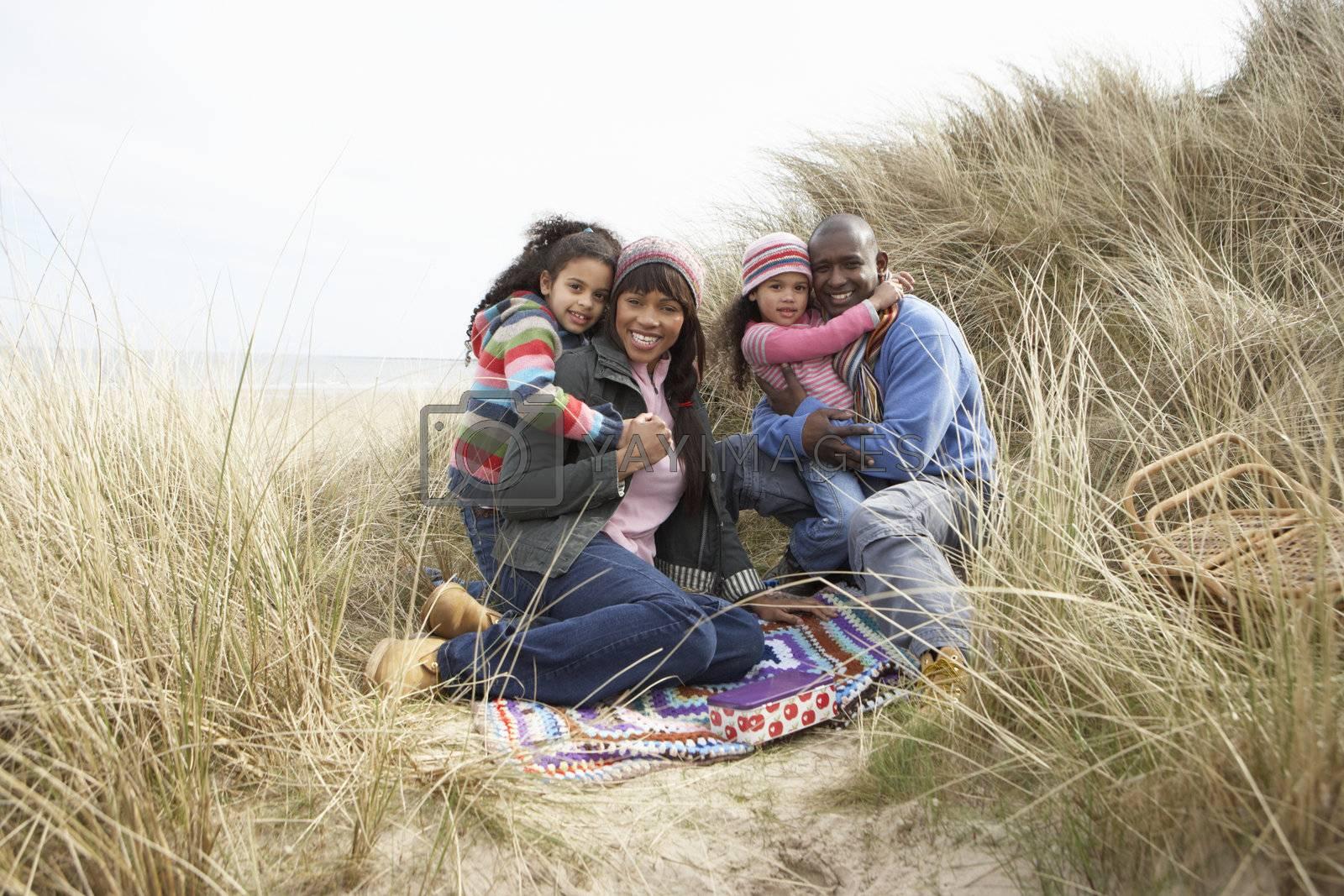 Family Sitting In Dunes Enjoying Picnic On Winter Beach