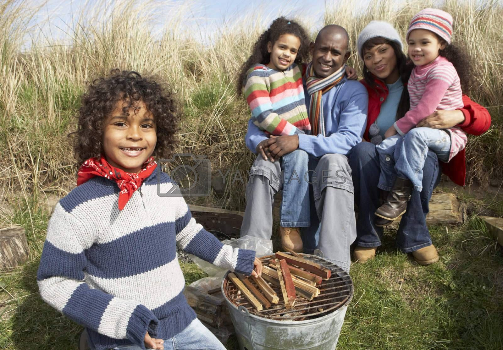 Family Having Barbeque On Winter Beach