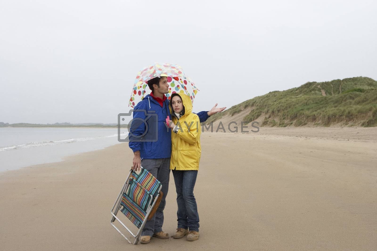 Royalty free image of Young couple on beach with umbrella by omg_images