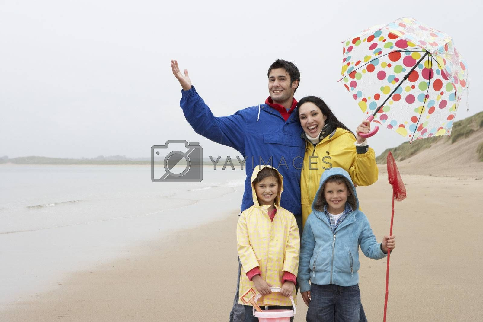 Royalty free image of Happy family on beach with umbrella by omg_images