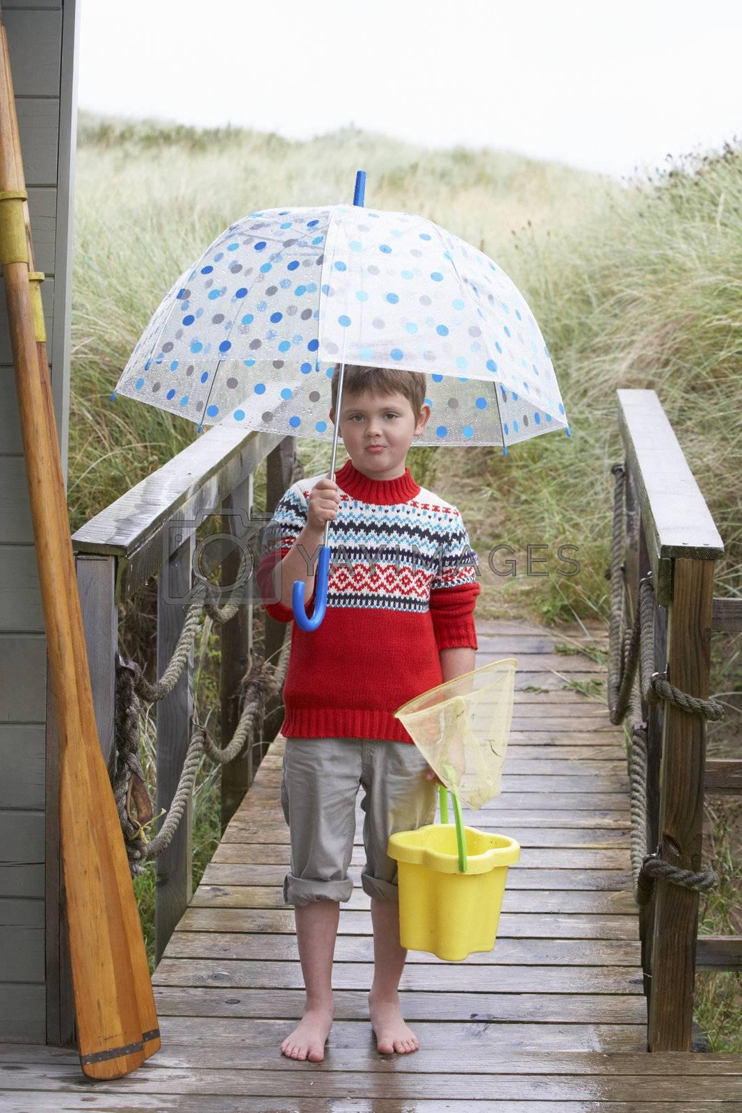 Boy standing on footbridge with umbrella