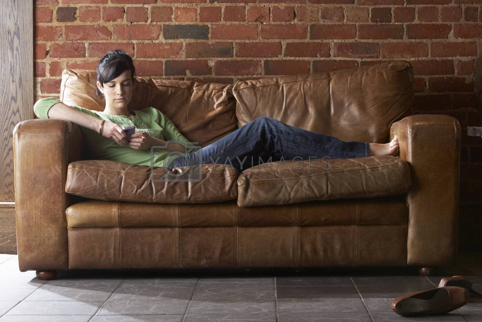 Young woman with phone on sofa