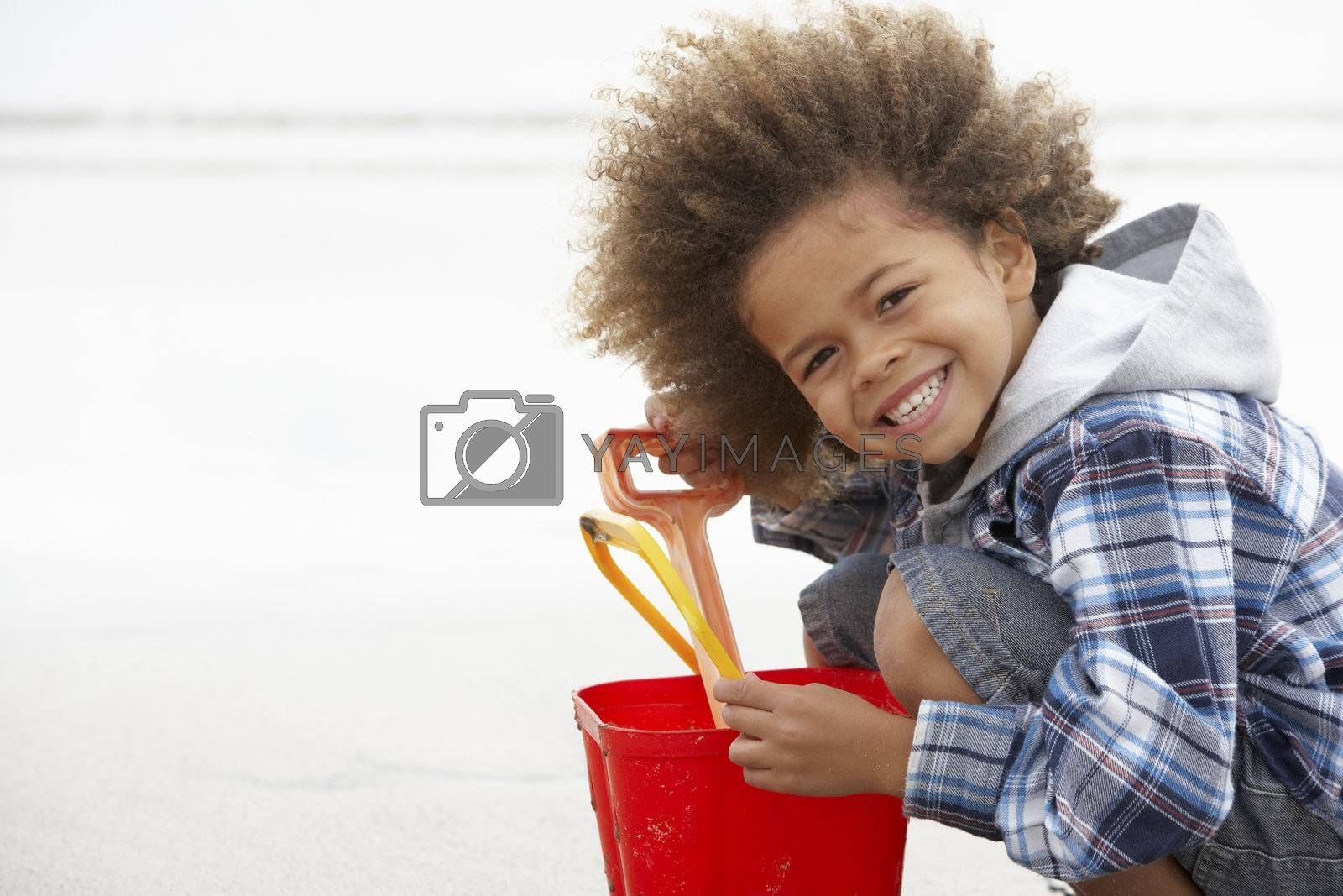 Happy boy at beach with bucket and spade