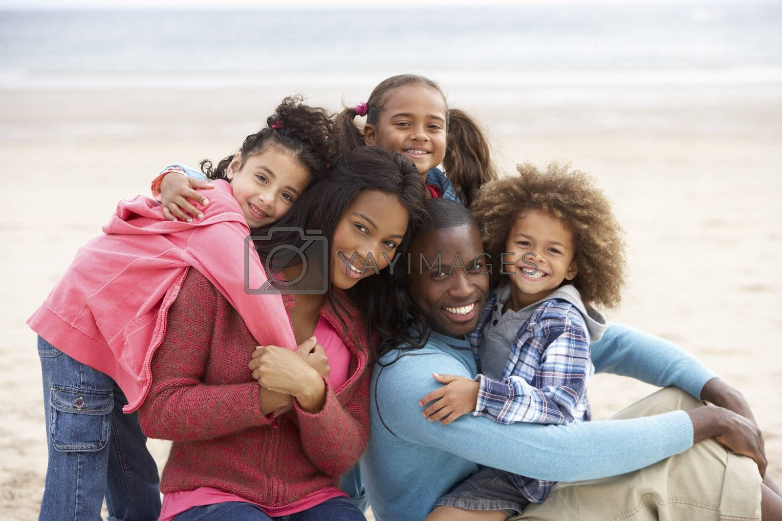 Royalty free image of Young mixed race family embracing on beach by omg_images