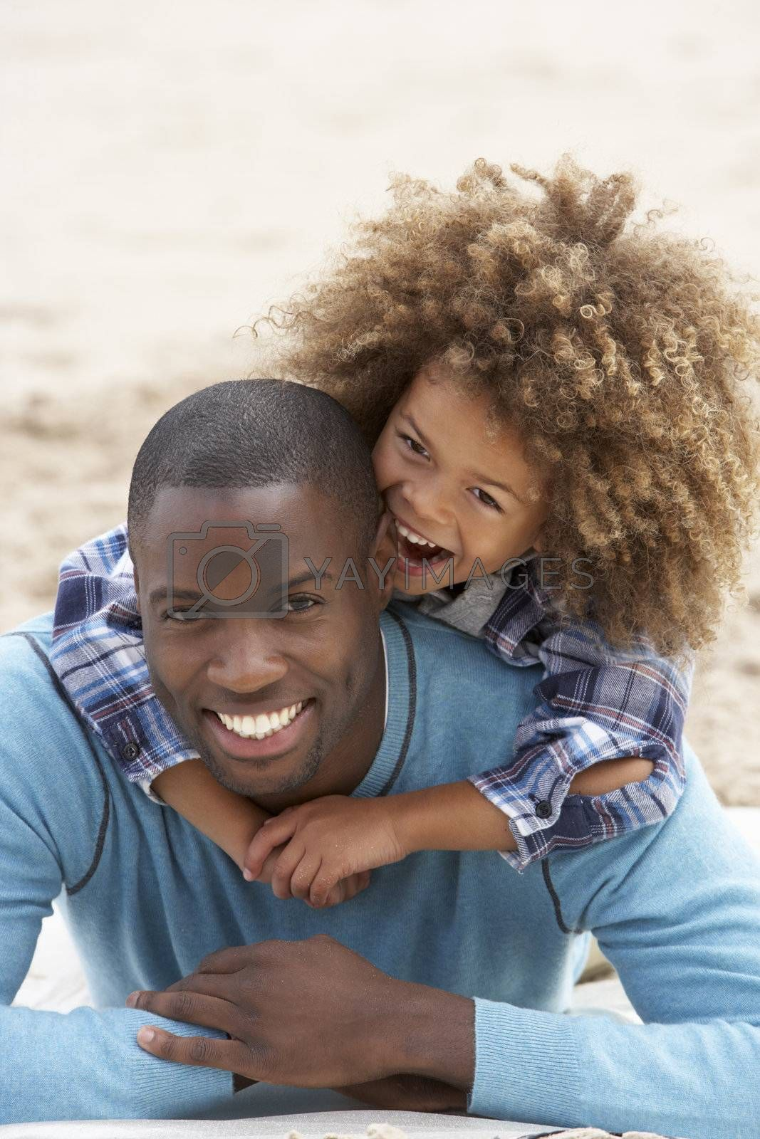 Royalty free image of Father and son playing piggyback on beach by omg_images