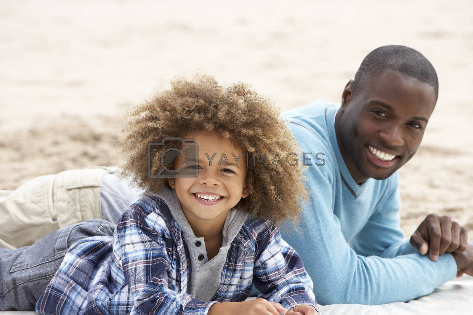 Royalty free image of Father and son laying on beach by omg_images