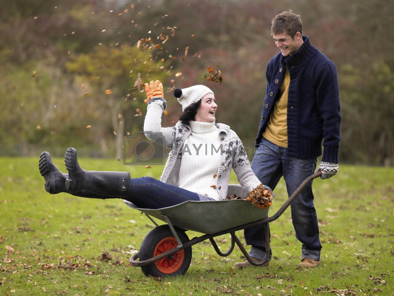 Royalty free image of Young couple playing in wheelbarrow by omg_images