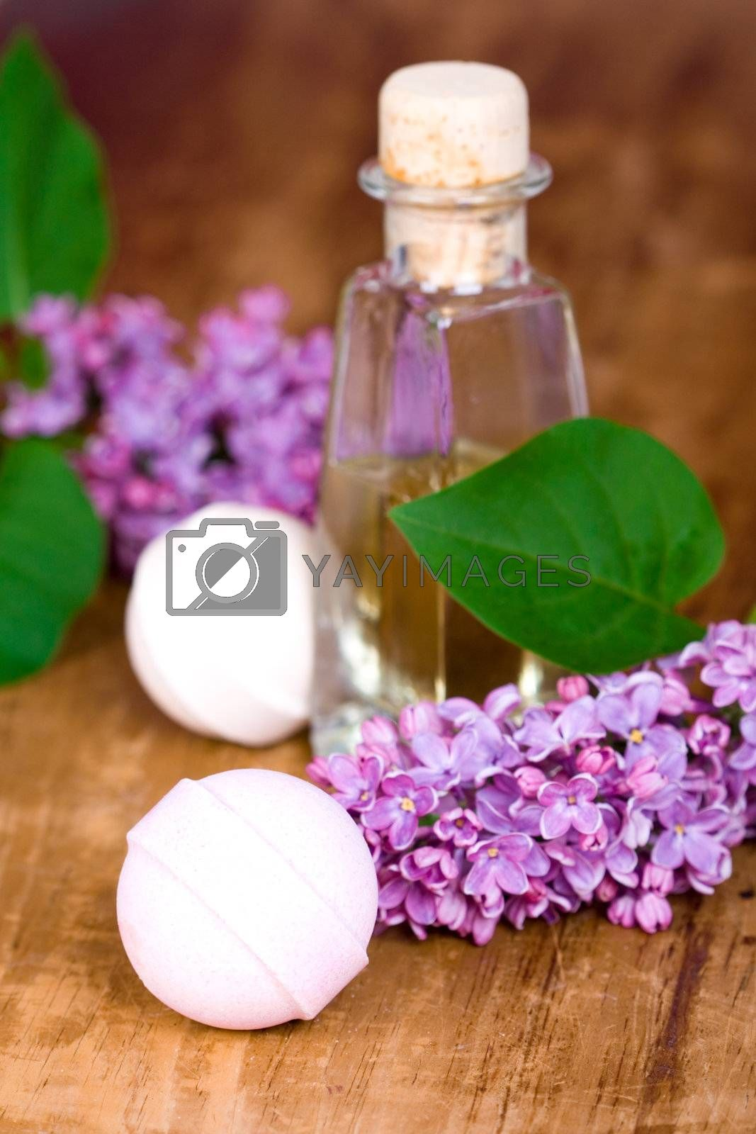 bath and spa items (oil, lilac, balls) on wooden background