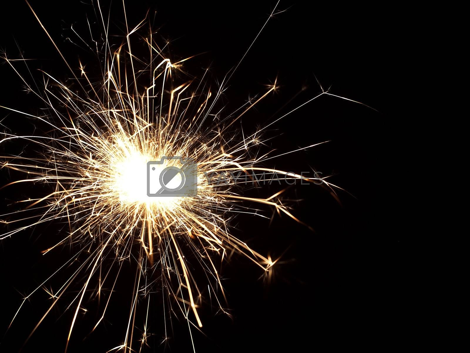 Details of a burning handheld firework over black background