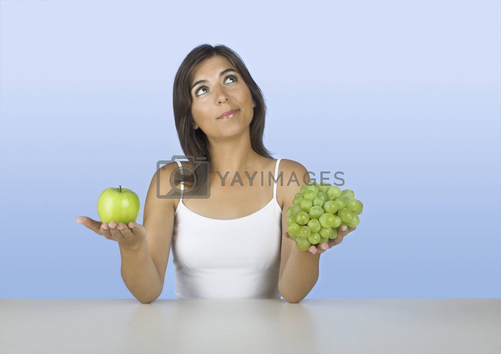 Beautiful young woman thinking on what to eat