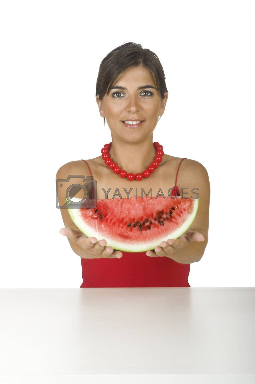 Beautiful young woman in the kitchen showing a watemelon slice in front of her