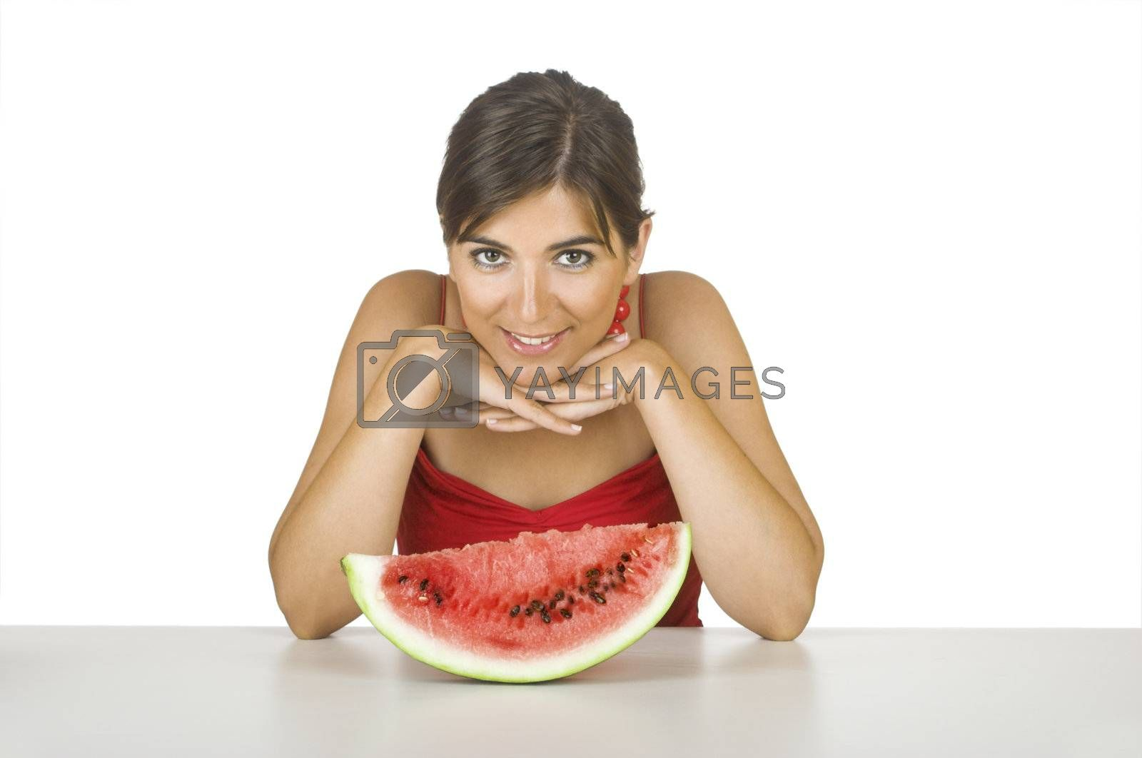 Beautiful young woman in the kitchen with a watemelon slice in front of her