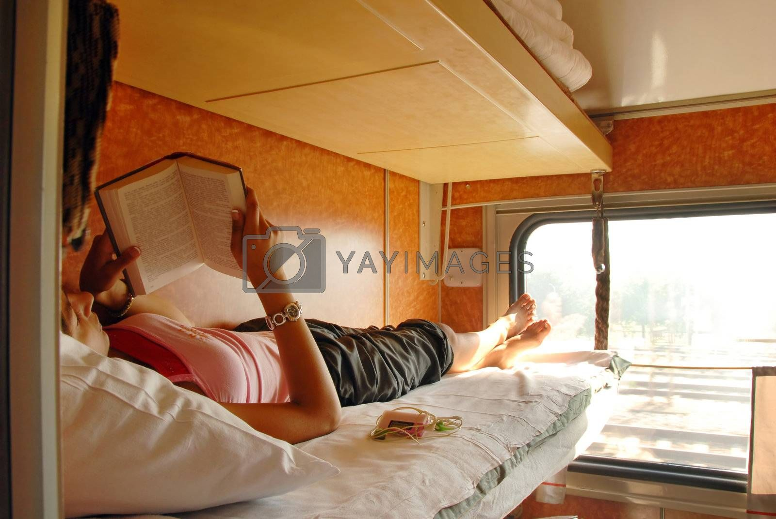 girl lying and reeding a book in sleeping wagon in train